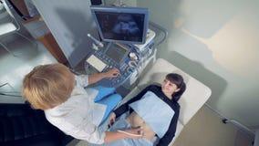 L'abdomen du ` s de femme enceinte passe par l'échographie banque de vidéos