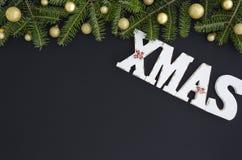 L'abete di Natale si ramifica con le decorazioni su un fondo nero Letterrs di legno bianchi di natale modello posto piano fotografia stock libera da diritti