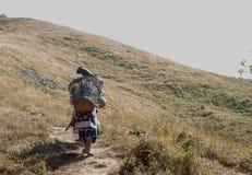 L'abitante degli altipiani scozzesi porta il trekking della borsa alla montagna fotografia stock libera da diritti