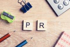 L'abréviation de RP sur la table a orthographié avec des éléments de jeu d'éducation Photographie stock libre de droits