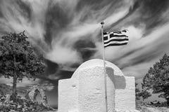 L'abside di una chiesa greca tipica con la bandiera nel vento fra le rovine del castello medievale Monolithos, Rodi, Grecia immagini stock