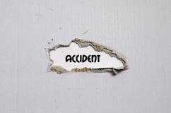 L'accident de mot apparaissant derrière le papier déchiré Image stock