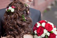 L'acconciatura di nozze con le rose ed il mazzo nuziale appoggiano la vista Fotografie Stock