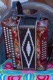 L'accordéon moderne rouge foncé de bouton se tient sur une chaise photos stock