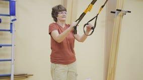 L'accroupissement de femme agée, faisant la physiothérapie s'exerce dans la chambre de forme physique Gymnastique saine Aînés act banque de vidéos