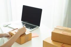 L'achat d'expédition en ligne, jeune commencent la petite adresse d'écriture d'entrepreneur sur la boîte en carton sur le lieu de photographie stock