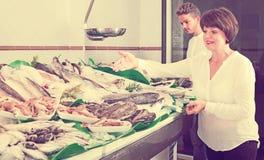 L'achat d'homme et de femme a refroidi sur des poissons de glace photos libres de droits