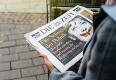 L'achat de femme allemand meurent journal de Zeit avec Angela Merkel Photos stock
