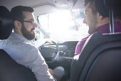 L'acheteur et le revendeur de sourire pendant un essai conduisent dans une voiture exclusive images stock