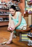 L'acheteur féminin essaye sur des sandales pour la saison d'été Image stock