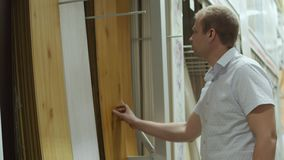L'acheteur masculin choisit le stratifié dans la boutique des matériaux de construction clips vidéos