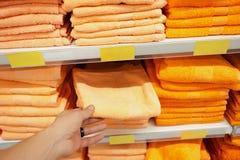 L'acheteur prend des serviettes de bain de couleurs lumineuses dans une rangée dans une rangée au compteur du compteur de magasin Photo stock