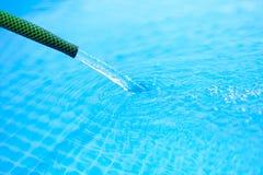 L'acqua è versata dal tubo flessibile nel raggruppamento Fotografia Stock Libera da Diritti