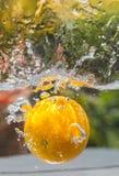 L'acqua arancio della frutta spruzza nel primo piano all'aperto Fotografia Stock Libera da Diritti