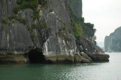L'acqua avvolge ad una caverna alla base di una scogliera del calcare nella baia di Halong Immagine Stock