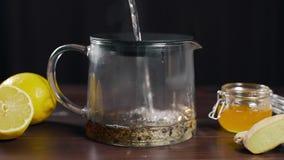 L'acqua bollente è versata alla teiera con tè nero, il tè della vitamina con il limone, lo zenzero ed il miele, bevanda contro la video d archivio