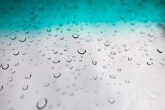 L'acqua cade la priorità bassa Gocce di acqua sulla finestra di vetro sopra la SK blu Fotografie Stock Libere da Diritti