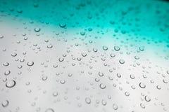 L'acqua cade la priorità bassa Gocce di acqua sulla finestra di vetro sopra la SK blu Fotografia Stock Libera da Diritti