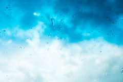 L'acqua cade la priorità bassa Gocce di acqua sulla finestra di vetro sopra la SK blu Immagine Stock
