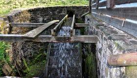 L'acqua cade sulla ruota nel pozzo Fotografie Stock Libere da Diritti