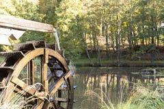 L'acqua commovente del vecchio mulino a acqua d'annata della ruota spruzza nello stagno fotografia stock