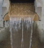L'acqua corrente scorre dalla fontana moderna della depressione concreta Fotografia Stock