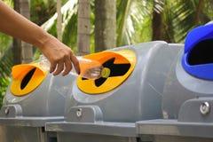 L'acqua di bottiglia di lancio della tenuta della mano della donna nel ricicla il recipiente fotografia stock