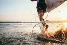 L'acqua di immagine del primo piano spruzza dalle gambe del ` s del surfista fatte funzionare nello spirito dell'oceano Immagini Stock
