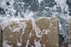 L'acqua di mare versa fuori delle pietre del frangiflutti mentre l'onda retrocede, Ogden Point, Victoria, BC immagini stock libere da diritti