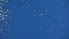 L'acqua di versamento su fondo blu con il lotto delle bolle di aria e spruzza al rallentatore video d archivio