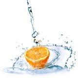 L'acqua dolce cade sull'arancio isolato su bianco Immagine Stock