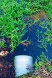 L'acqua entra in un tubo di straripamento bianco da uno stagno fotografie stock