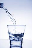 L'acqua ha versato in vetro Fotografie Stock Libere da Diritti
