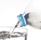 L'acqua potabile è versata da una bottiglia in un vetro sul BAC bianco Fotografia Stock