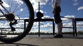 L'acqua potabile del ciclista stancato da una bottiglia da restare nel campo vicino alla diga sui precedenti delle settimane dell video d archivio