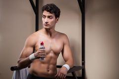 L'acqua potabile dell'uomo assetato nella palestra di sport Fotografia Stock