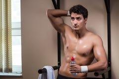 L'acqua potabile dell'uomo assetato nella palestra di sport Fotografie Stock