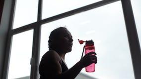 L'acqua potabile della donna dell'atleta da imbottiglia il movimento lento nella palestra video d archivio