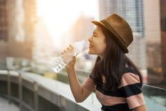 L'acqua potabile della ragazza asiatica da imbottiglia la luce di mattina Immagini Stock