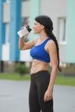 L'acqua potabile di riposo della bella di forma fisica donna dell'atleta dopo risolve l'esercitazione sulla sera dell'estate dell fotografie stock libere da diritti