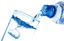L'acqua pura è versata da una bottiglia in un vetro Fotografia Stock Libera da Diritti