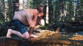 L'acqua pura della bevanda dalla mano del ` s dell'uomo del fiume della montagna è assorbita dall'acqua pura dal fiume della mont stock footage