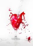 L'acqua rossa straripa il vetro di vino rotto su un fondo bianco Immagine Stock