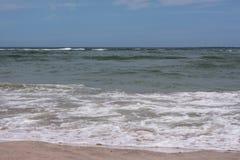 L'acqua sulla spiaggia sta spumando Immagine Stock