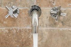 L'acqua versa da un rubinetto moderno Fotografia Stock