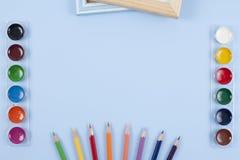 L'acquerello e le spazzole al piano blu del fondo pongono la vista superiore Immagini Stock