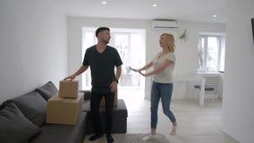 L'acquisto dell'appartamento, coppie allegre porta le scatole e la delizia che comprano gli alloggi nuovi durante l'inaugurazione archivi video