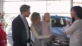 L'acquisto dell'automobile di famiglia, genitori felici del cliente con la piccola figlia consulta la venditora sull'acquisto del