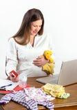 L'acquisto della donna incinta per il bambino fornisce online Fotografia Stock