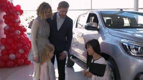 L'acquisto felice dell'automobile di famiglia, venditora sorridente mette digita le mani di poco bambino con i genitori ai nuovi